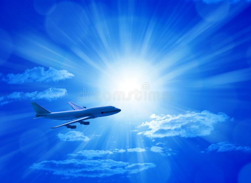 Airplane Flying Blue Sky. An airplane flying through a blue sunny sky royalty free stock photo