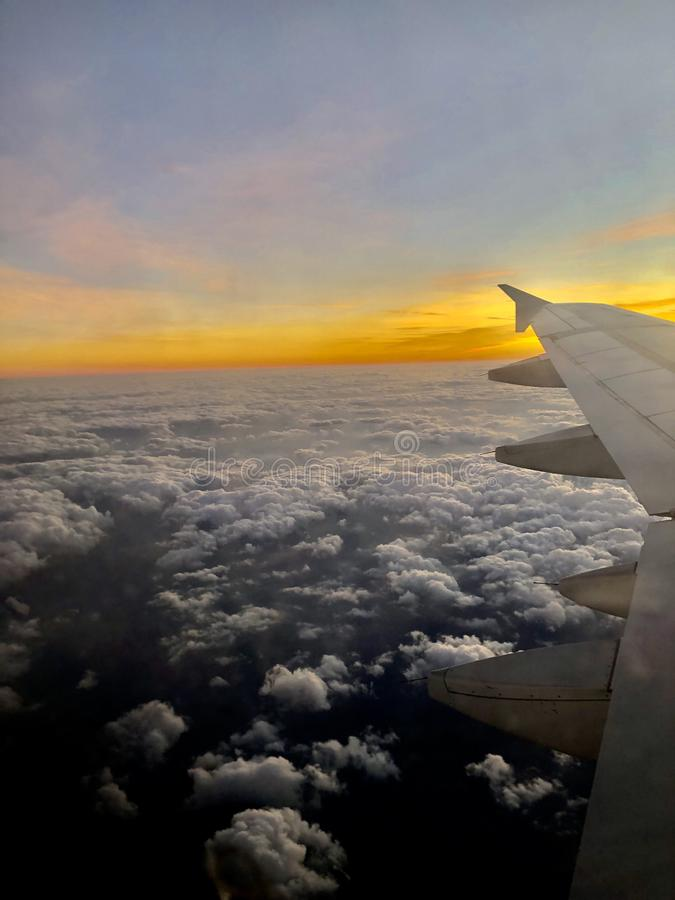 Airplane flying over beautiful clouds stock image