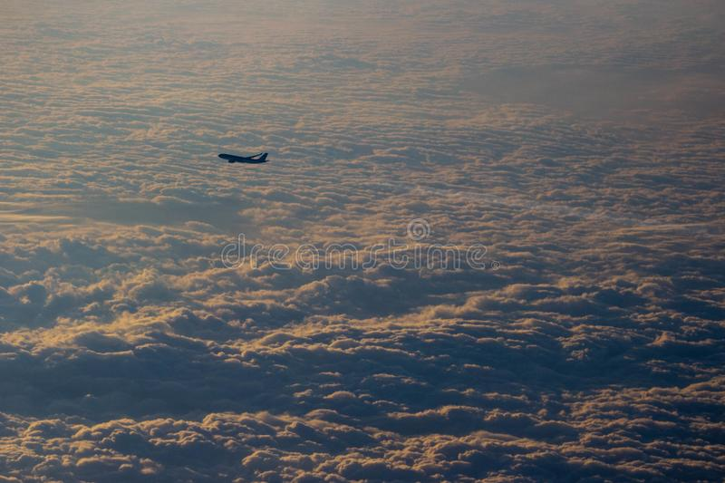 Airplane leaving a contrail seen from another airplane on a moody carpet of clouds during sunset stock image