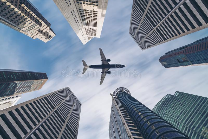 Airplane flying over city business buildings, high-rise skyscrapers royalty free stock image