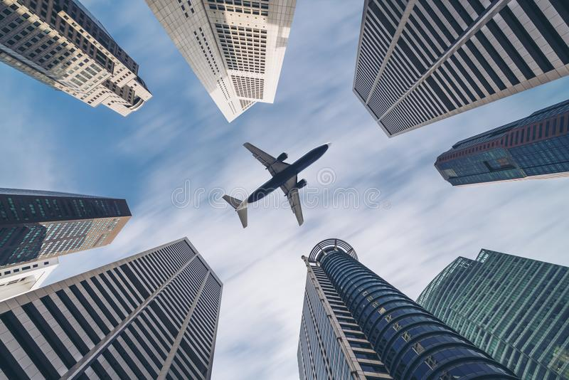 Airplane flying over city business buildings, high-rise skyscrapers. Airplane flying over city buildings, high-rise business skyscrapers. Tourism, transport stock photos
