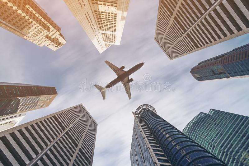 Airplane flying over city business buildings, high-rise skyscrapers stock image