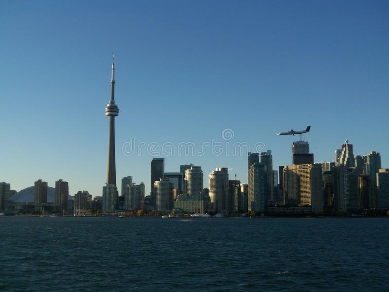 Airplane flying over Downtown Toronto Ontario Canada skyline view from Lake Ontario. Skyscraper, tower, buildings, urban, city, travel, tourism, clearsky stock photo