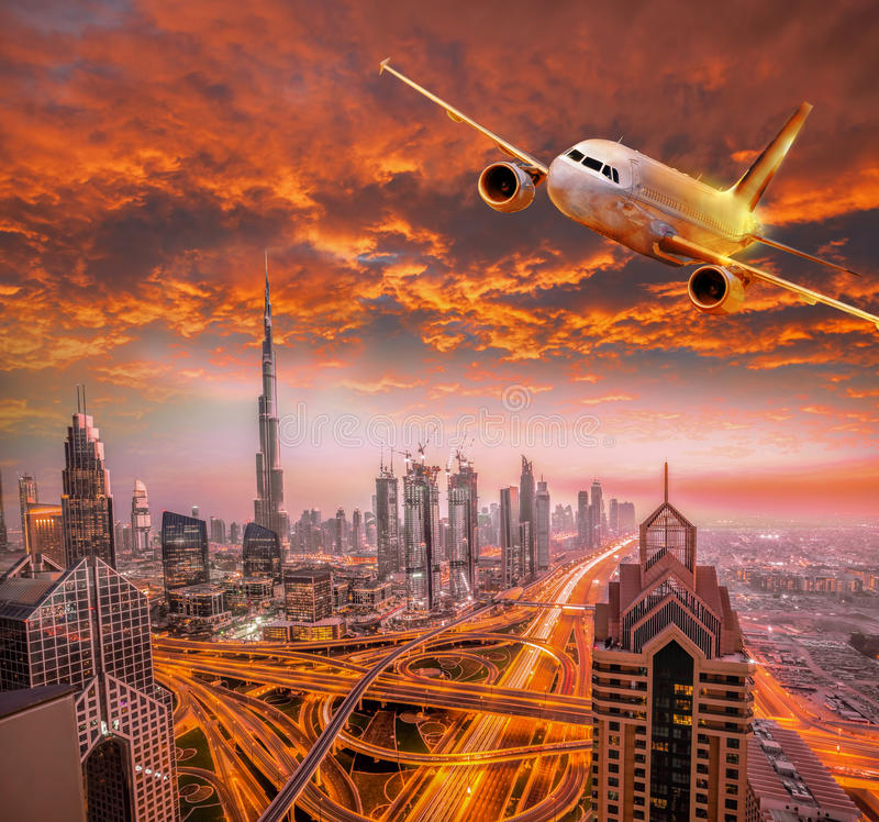 Airplane is flying over Dubai against colorful sunset in United Arab Emirates. Airplane is flying over famous Dubai against colorful sunset in United Arab royalty free stock image