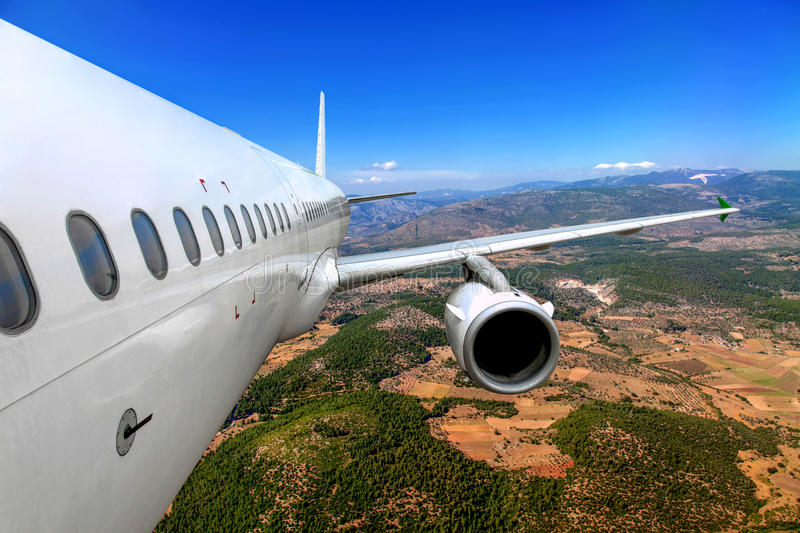 Airplane flying over the ground. Passenger airplane flying over the ground stock images