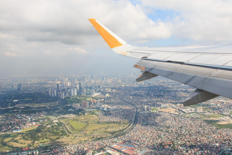 Airplane flying over Manila, Philippines.  stock image