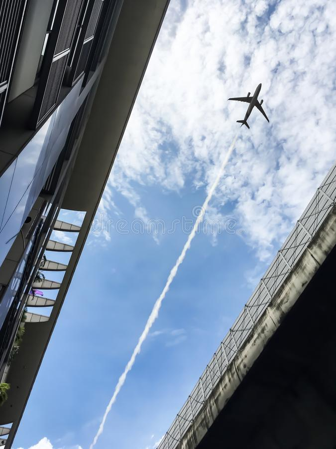 Airplane flying over between modern architecture and expressway. stock photo