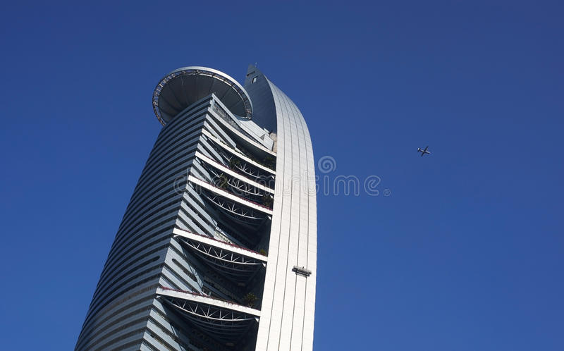 Airplane is flying over the modern building stock image