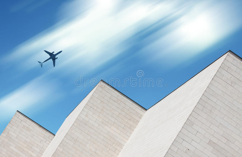 Airplane flying over modern building royalty free stock image