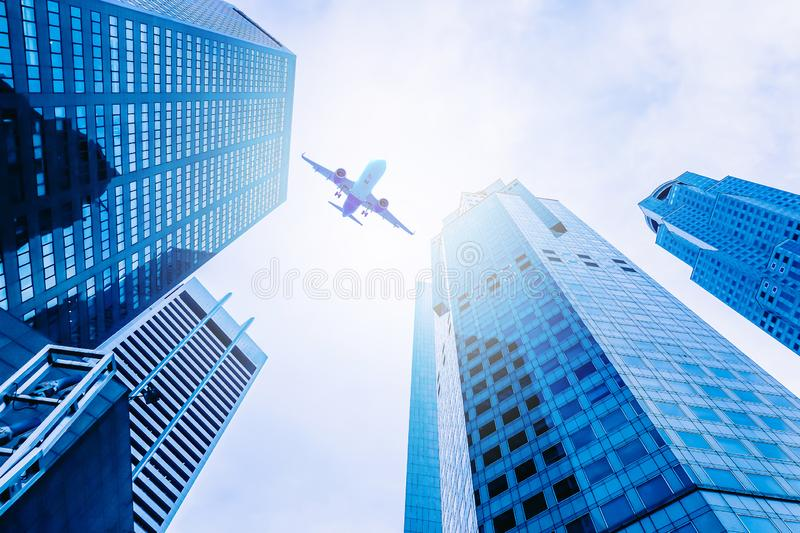 Airplane flying over modern glass and steel office buildings in singapore stock photography