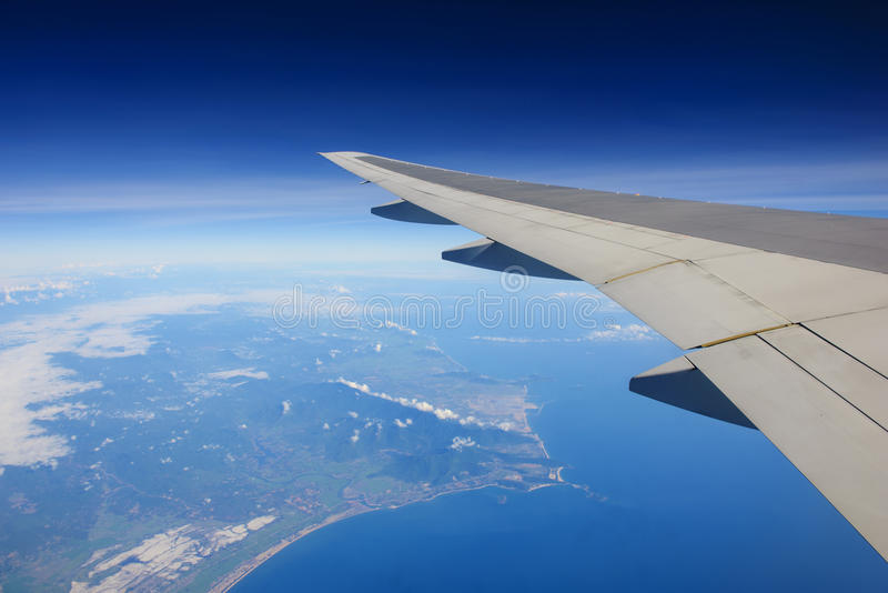 Airplane flying over ocean and island. Passenger view from airplane flying over ocean and island royalty free stock image
