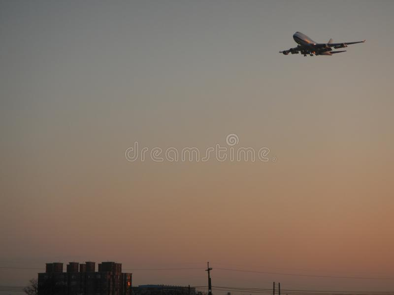 An airplane flying over residential building royalty free stock images