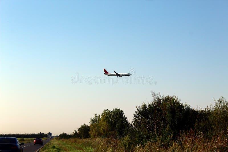 Airplane flying over road. Airplane flying over the road royalty free stock image