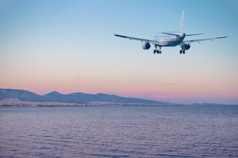 Airplane flying over the sea and beach at sunset. Travel concept royalty free stock photo
