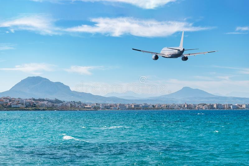 Airplane flying over the sea and beach. Travel concept.  stock photography