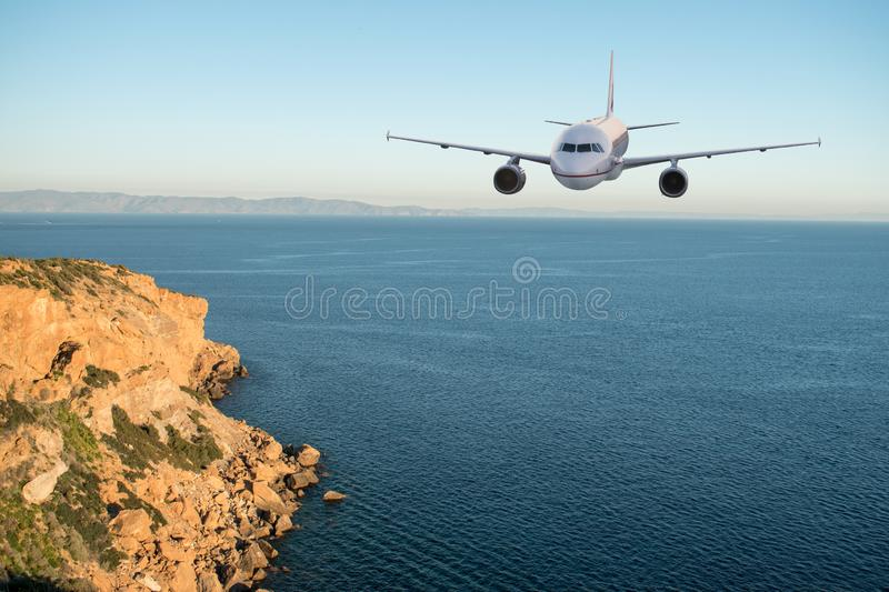 Airplane flying over the sea and mountains. Travel concept stock image