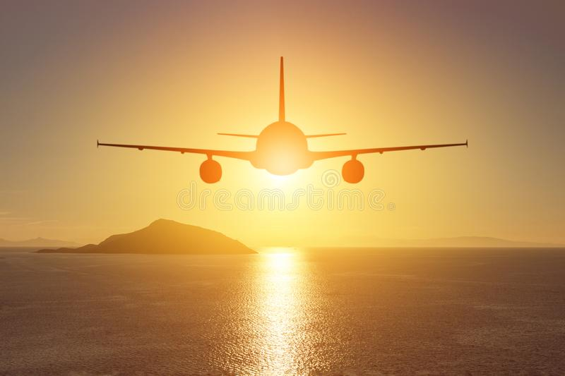 Airplane flying over the sea at sunset. Travel concept.  stock photography