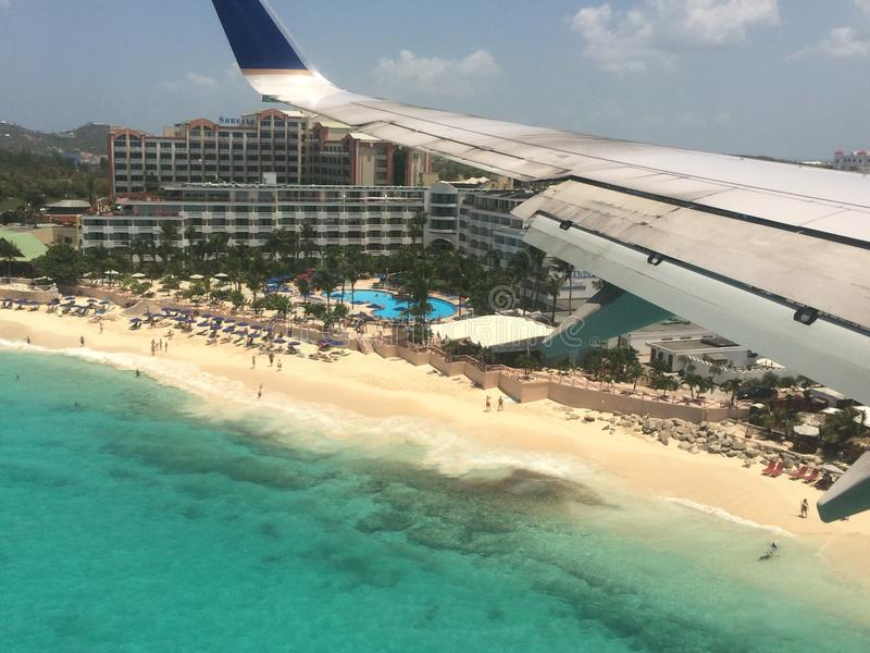 Airplane flying over St. Maarten beach royalty free stock photography