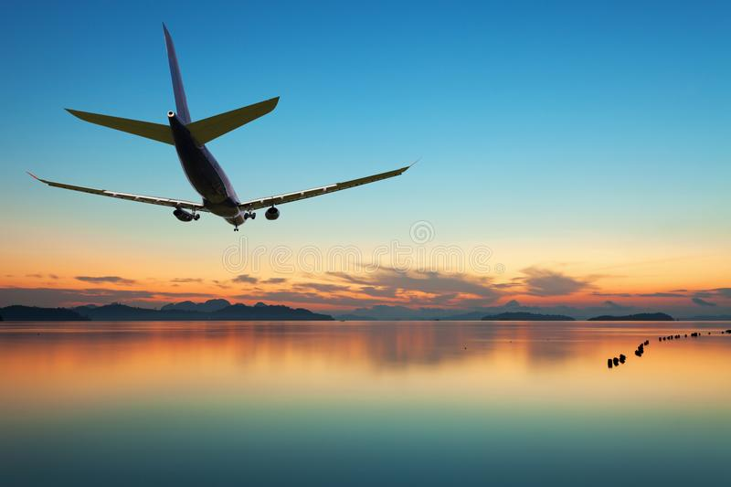 Airplane flying over tropical sea at beautiful sunset or sunrise. Scenery background stock image