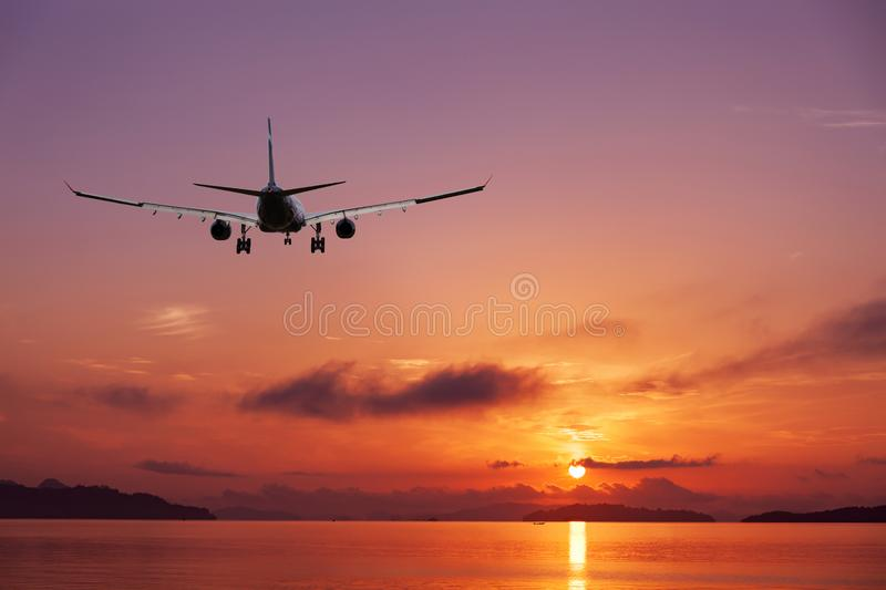 Airplane flying over tropical sea at beautiful sunset or sunrise. Scenery background,Beautiful sweet purple color scenery view of seascape in phuket thailand royalty free stock photos