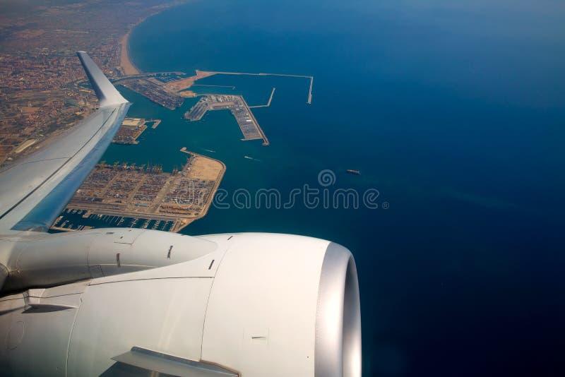 Airplane flying over Valencia Mediterranean port Spain stock photos