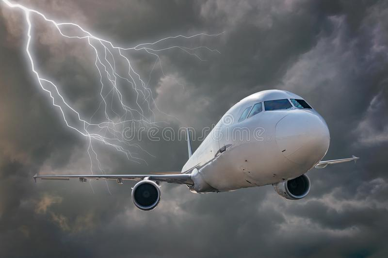 Airplane is flying in storm. Dark clouds and lightning in background royalty free stock photo