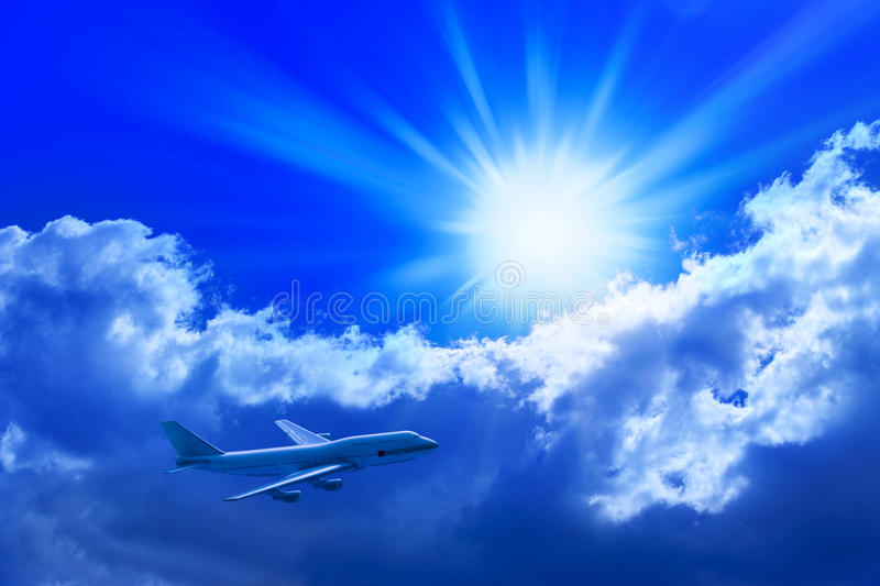 Airplane Flying Sun Sky. An airplane flying through a blue sky with the sun and clouds in the background royalty free stock photo