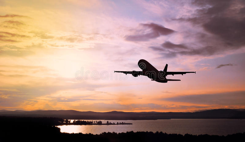 Airplane flying in the sunset sky over the water and mountains - oicturesque cloudscape stock image