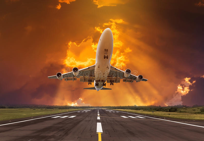 Airplane flying take off from runway on sunset royalty free stock image