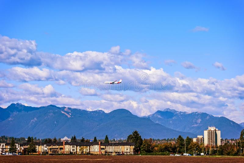Airplane flying under the clouds over the buildings royalty free stock photography