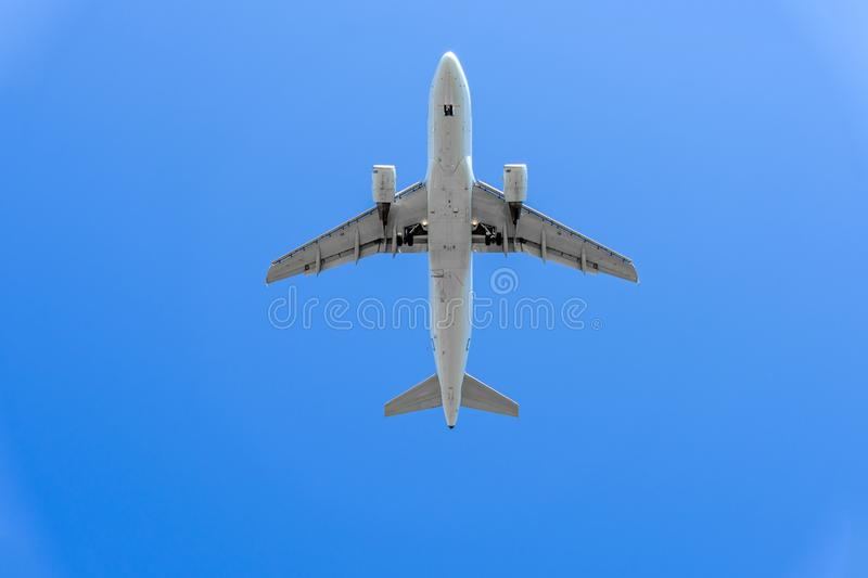 Airplane flying under the sky. White airplane flying under the blue sky. bottom view. Very big royalty free stock photo