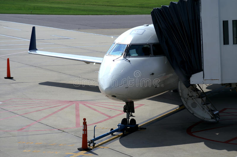 Airplane With Footbridge Being Attched stock images