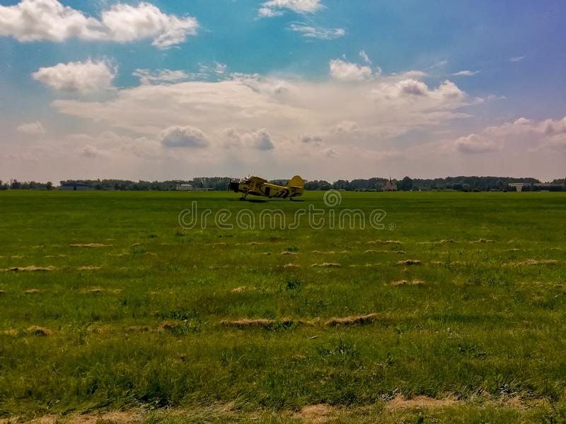 An2 airplane and green grass. Field, yellowairplane, airfield, airport, sky, clouds, poland, europe, airplanes royalty free stock images