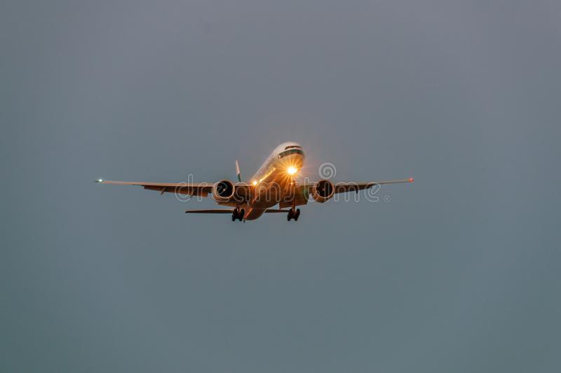 Airplane in the grey sky at night with headlight royalty free stock images