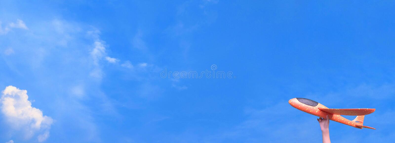 Airplane in hand fly in blue sky copy space and white cloud. Travel abroad in holiday. Childhood dreams aviation concept. Journey stock image