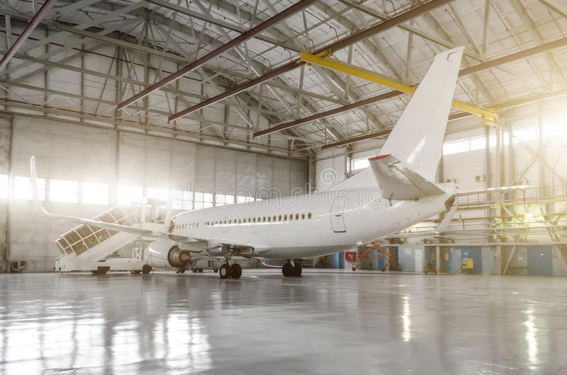 The airplane in the hangar, behind the whole plane and the gangway. royalty free stock images