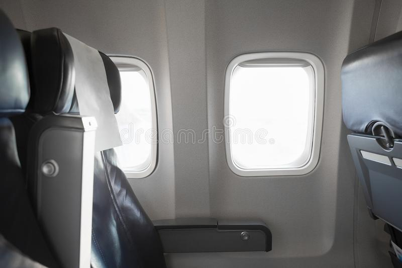 Airplane interior cabine and windows with empty passengers` seats royalty free stock image