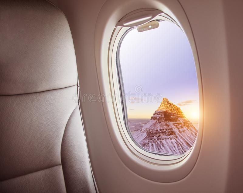 Airplane interior with window view of Kirkjufell mountain, Iceland. royalty free stock photos