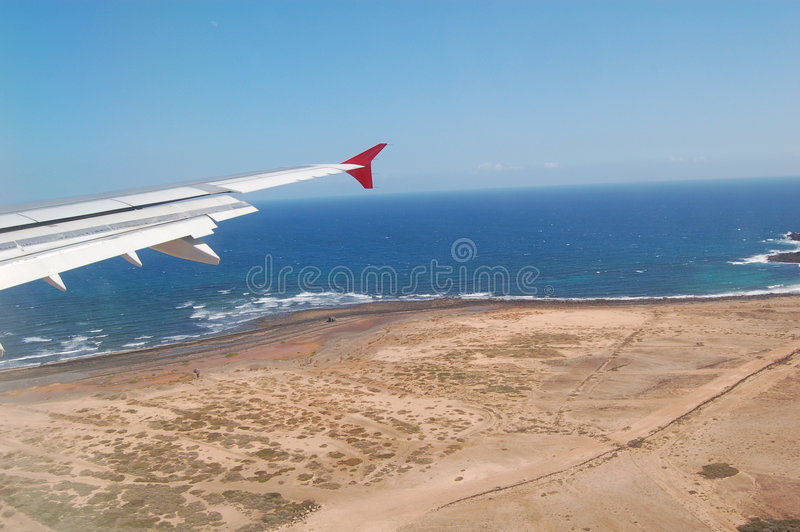 Airplane landing. Airplane wing against blue ocean and the sandy shore before landing in Puerto del Rosario, Fuerteventura, aerial view stock images
