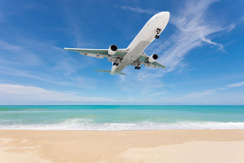 Airplane landing above beautiful beach and sea background. royalty free stock image