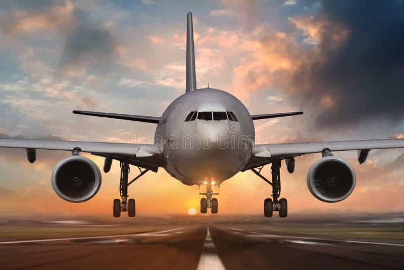 Airplane landing on airport runways during sunset stock photos