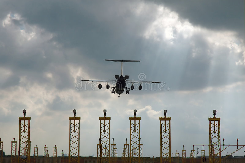 Airplane landing approach. Airplane just before touchdown on a grey and cloudy day with sun shining through the clouds stock photo