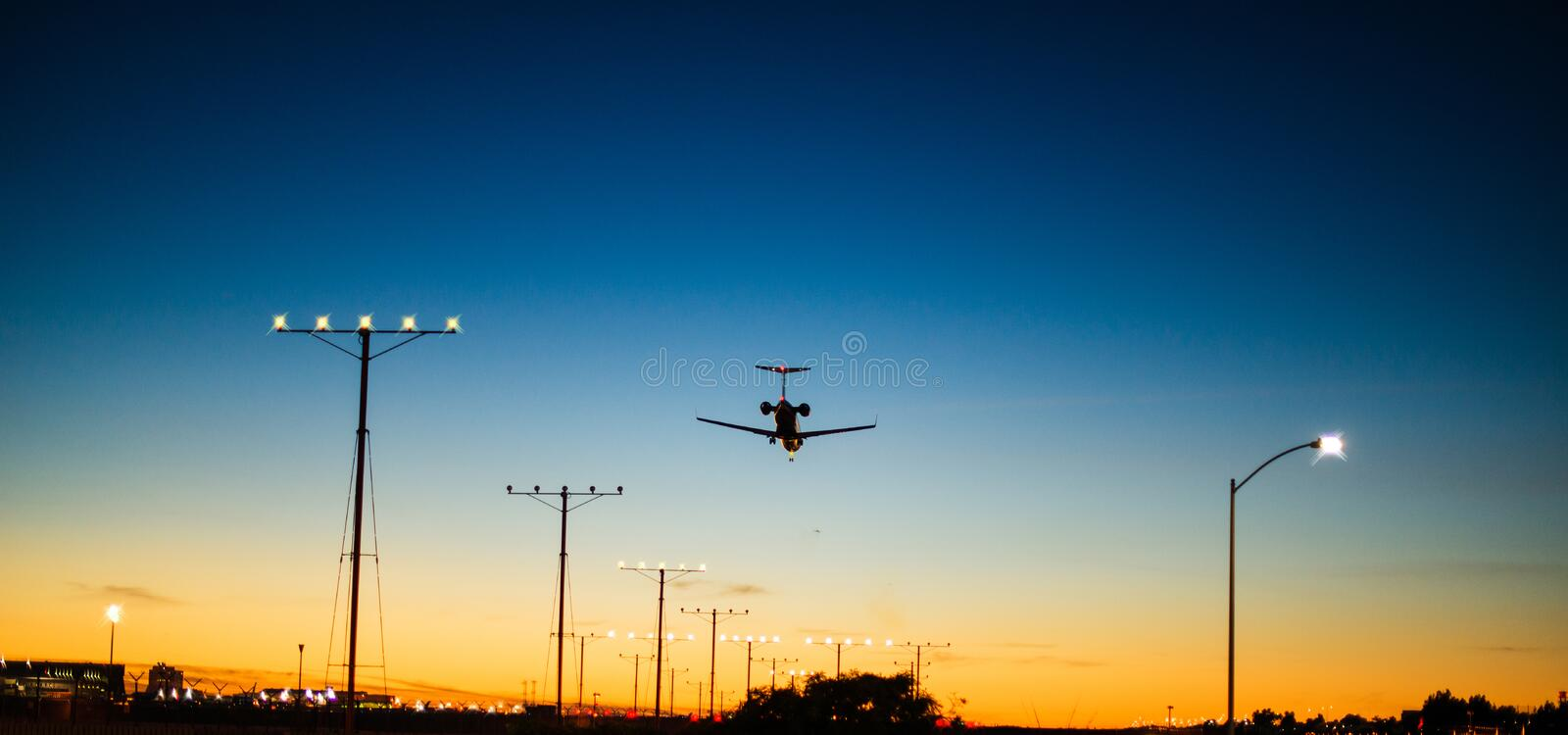 Airplane landing during dawn just before sunrise stock images