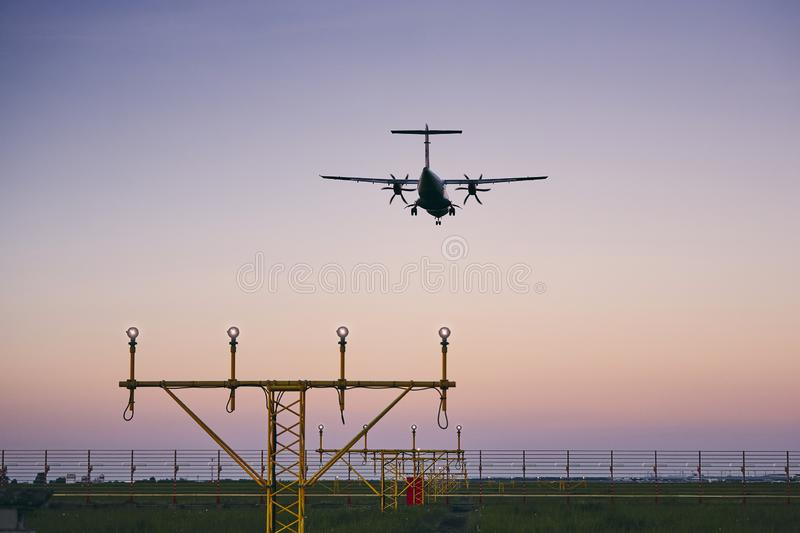 Airplane landing at dusk royalty free stock image