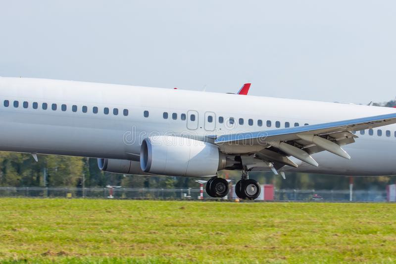 Airplane landing on runway touchdown close up side view fuselage stock image