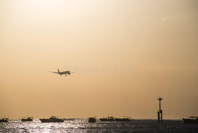 Airplane during landing at sunset stock image