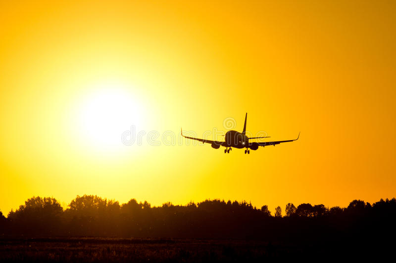 Airplane landing during sunset stock photography