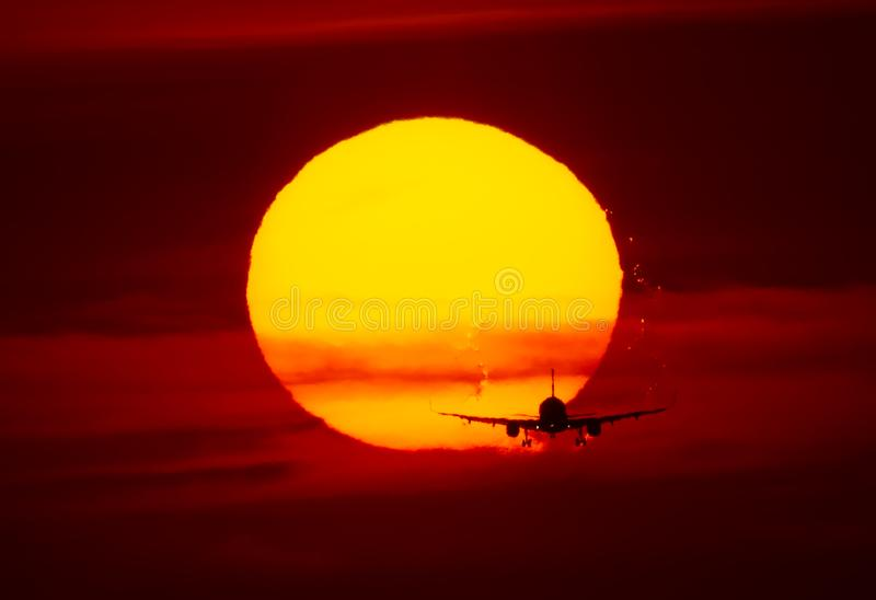 Airplane landing or takeoff in the sunset with red sky in Bucharest international airport , Plain spotting. And aviation photography with sun crossing royalty free stock photos