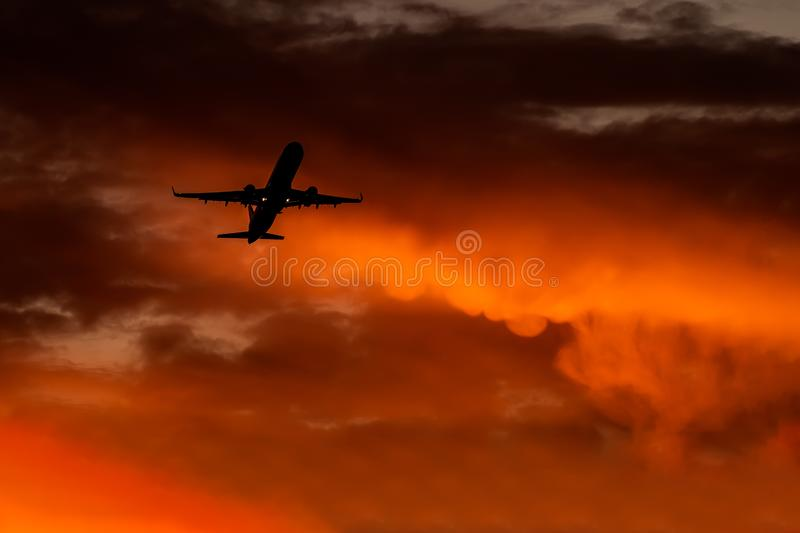 Airplane landing or takeoff in the sunset with red sky in Bucharest international airport , Plain spotting. And aviation photography with sun crossing stock photos