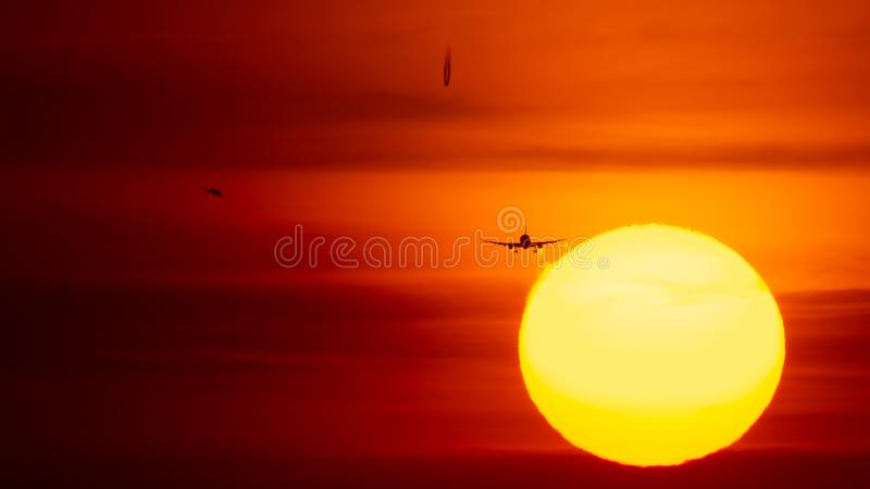 Airplane landing or takeoff in the sunset with red sky in Bucharest international airport , Plain spotting stock photography